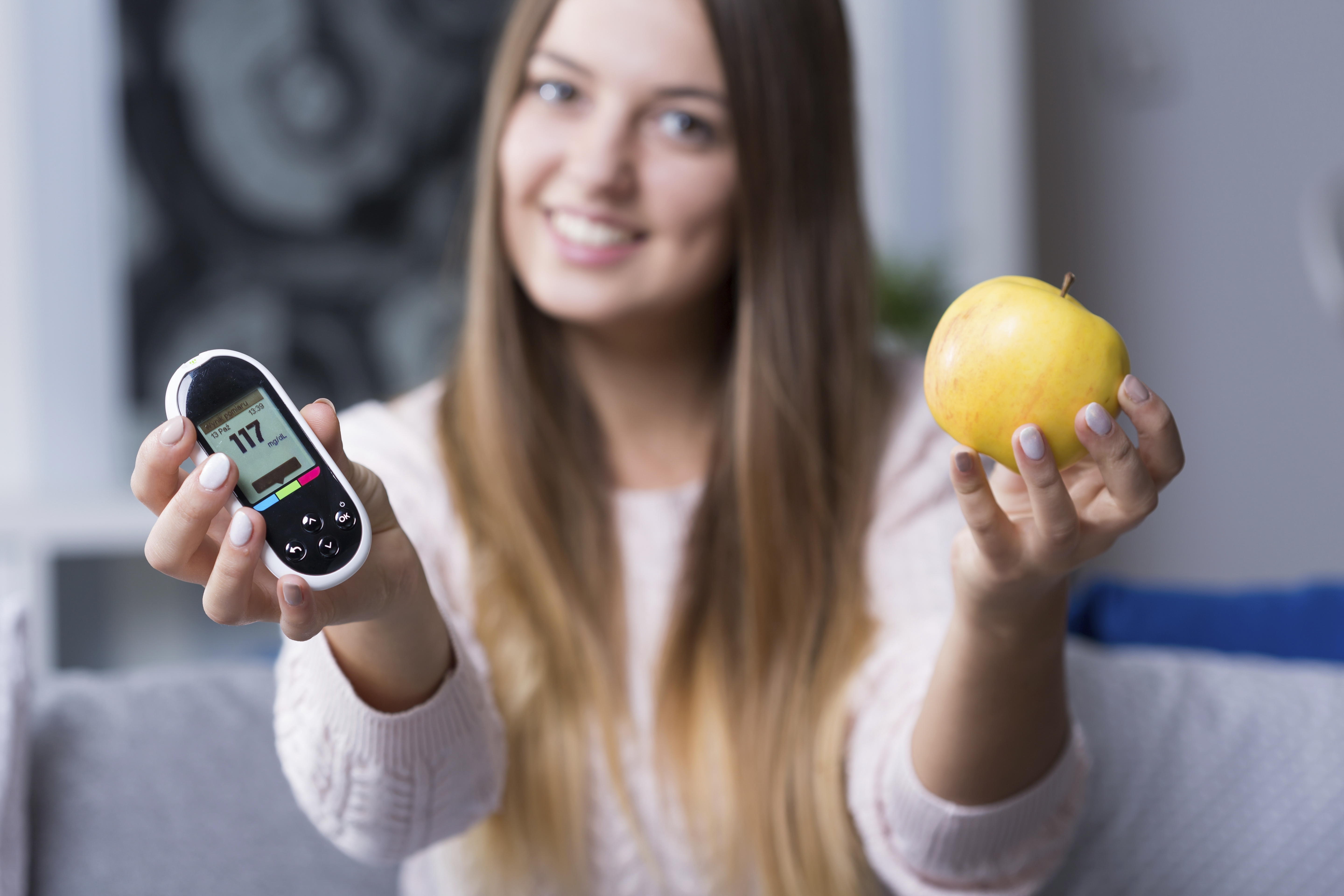 Young diabetic woman holding glucometer and apple
